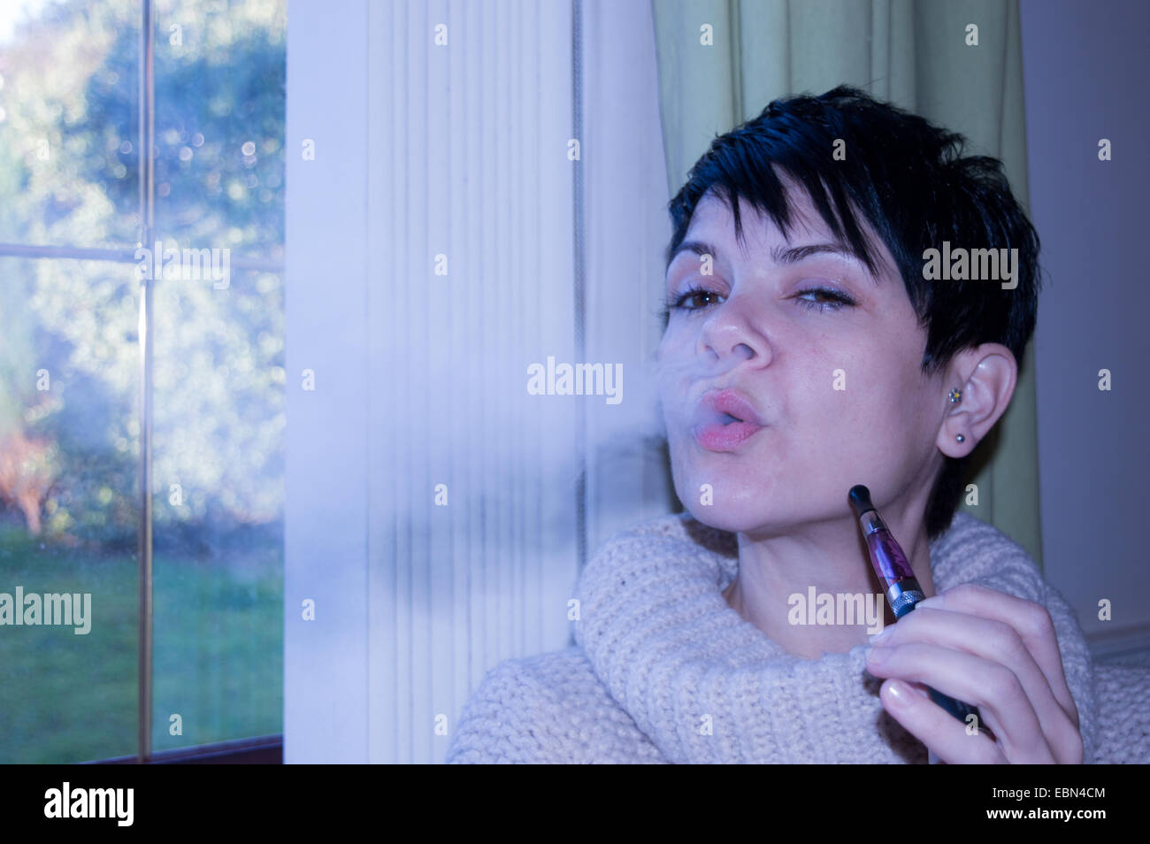 Are e-cigarettes cool?  Beautiful, short dark-haired woman vaping and blowing smoke into camera sat at window pensively - Stock Image