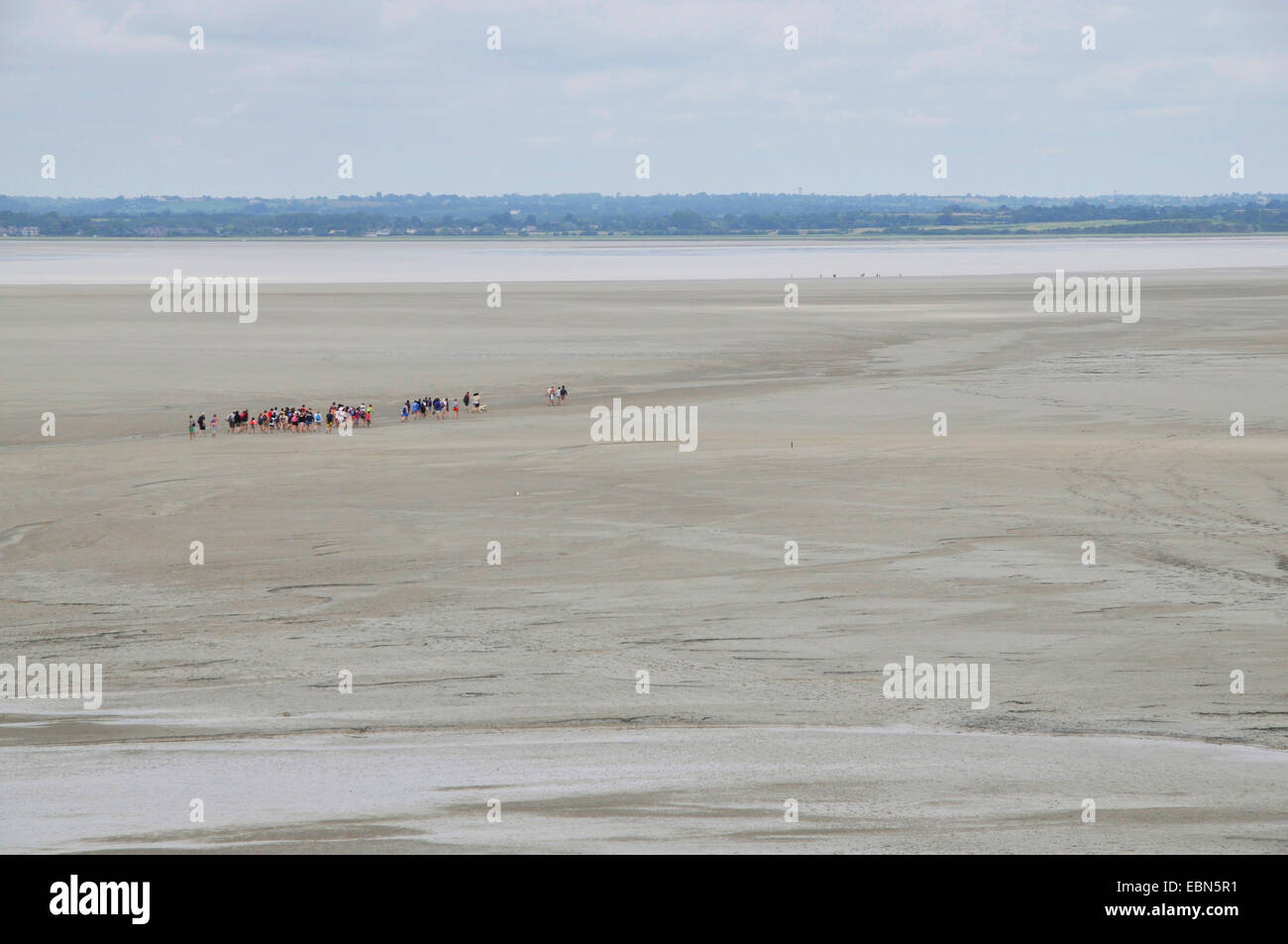 vastness outlook from the Mont Saint Michel on tidal flat hikers in the mud flat, France, Normandy - Stock Image