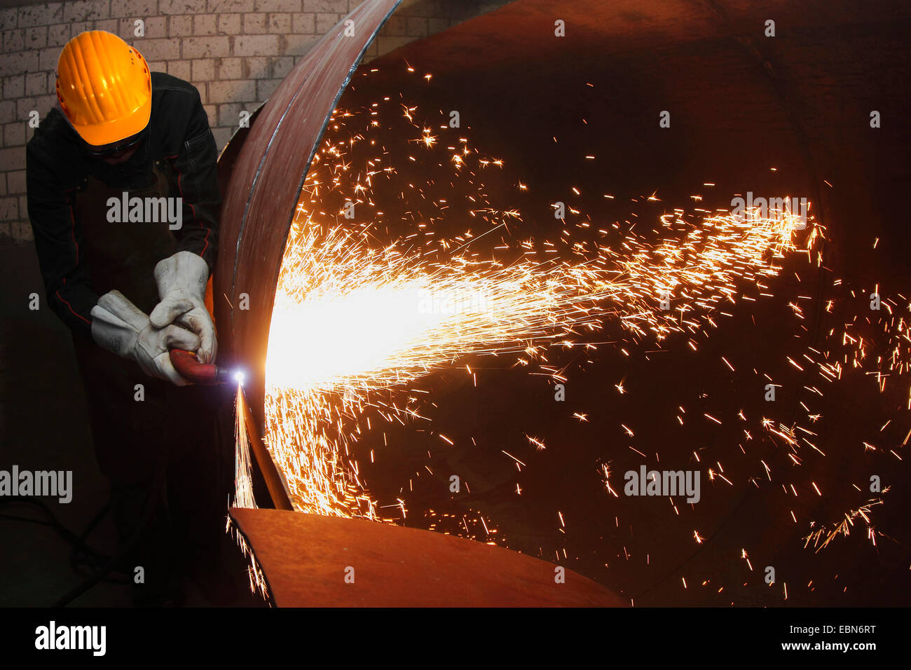 craftsman dismantles an oil tank with a plasma cutter - Stock Image