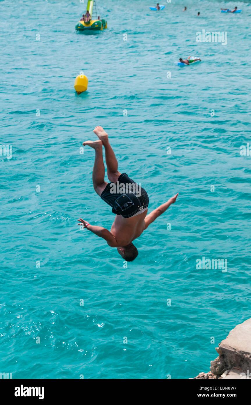 Young man somersaulting off the cliffs near Calas de Mallorca on Majorca Stock Photo