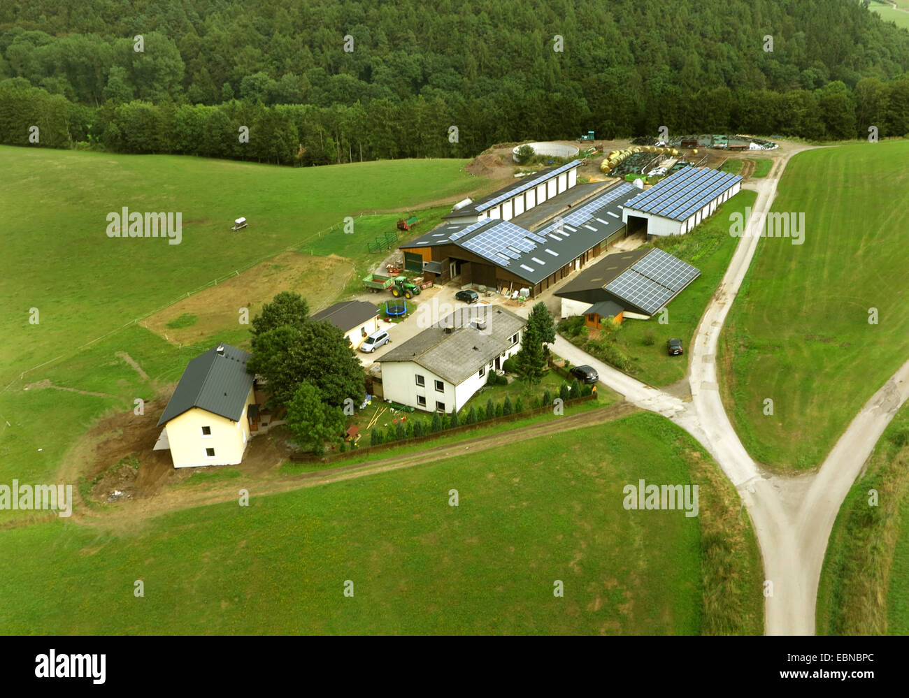 aerial view to farmhouses in Welleringhausen and stables with solar roofes, Germany, Hesse, Sauerland, Willingen - Stock Image