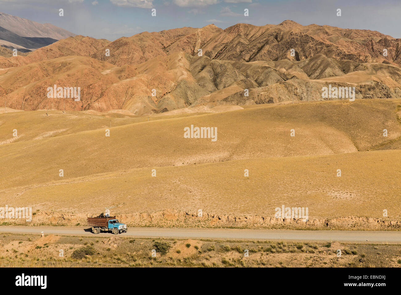 old truck on country road in hilly wasteland, Kyrgyzstan, Kochkor - Stock Image