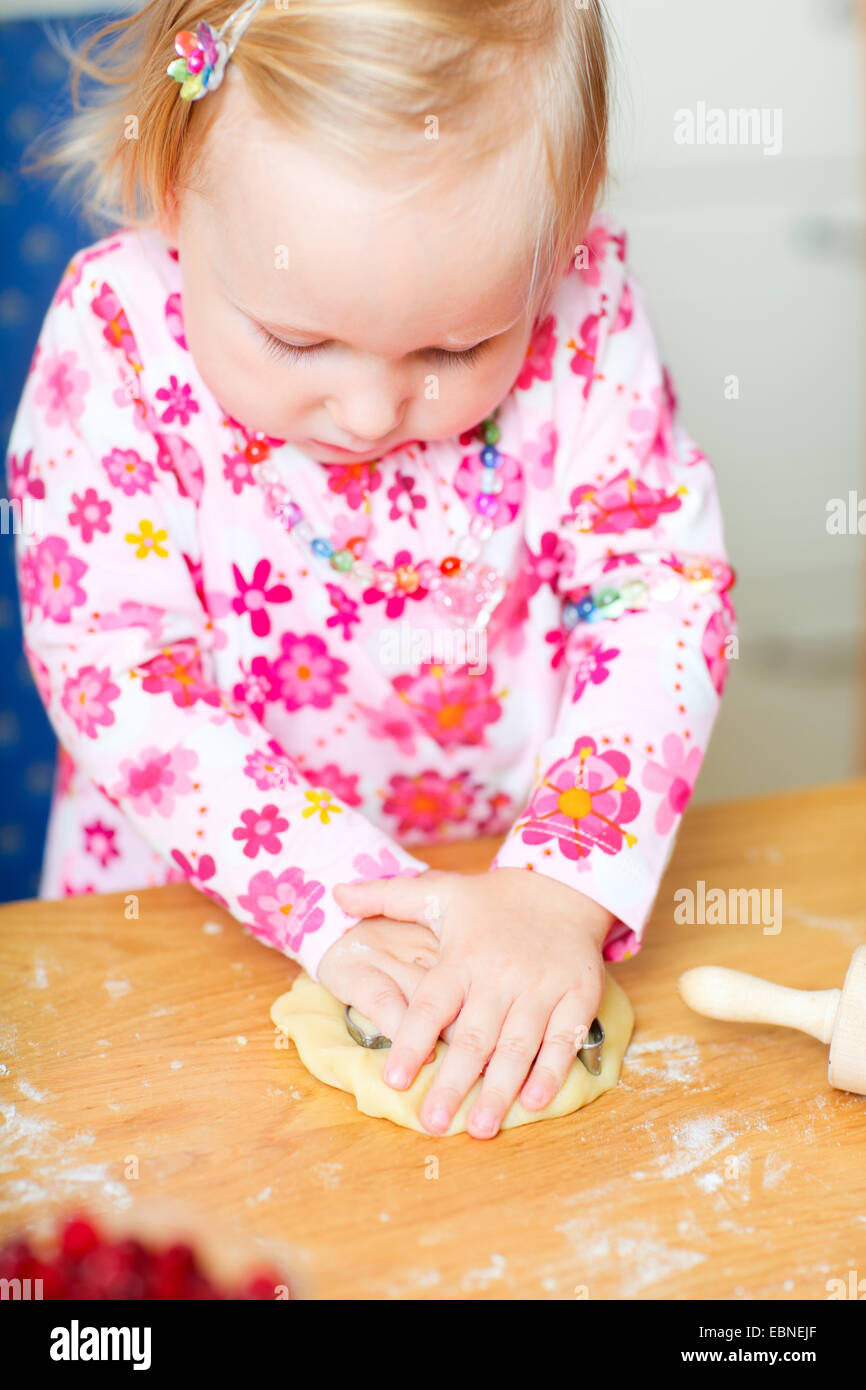 little girl using a biscuit cutter - Stock Image