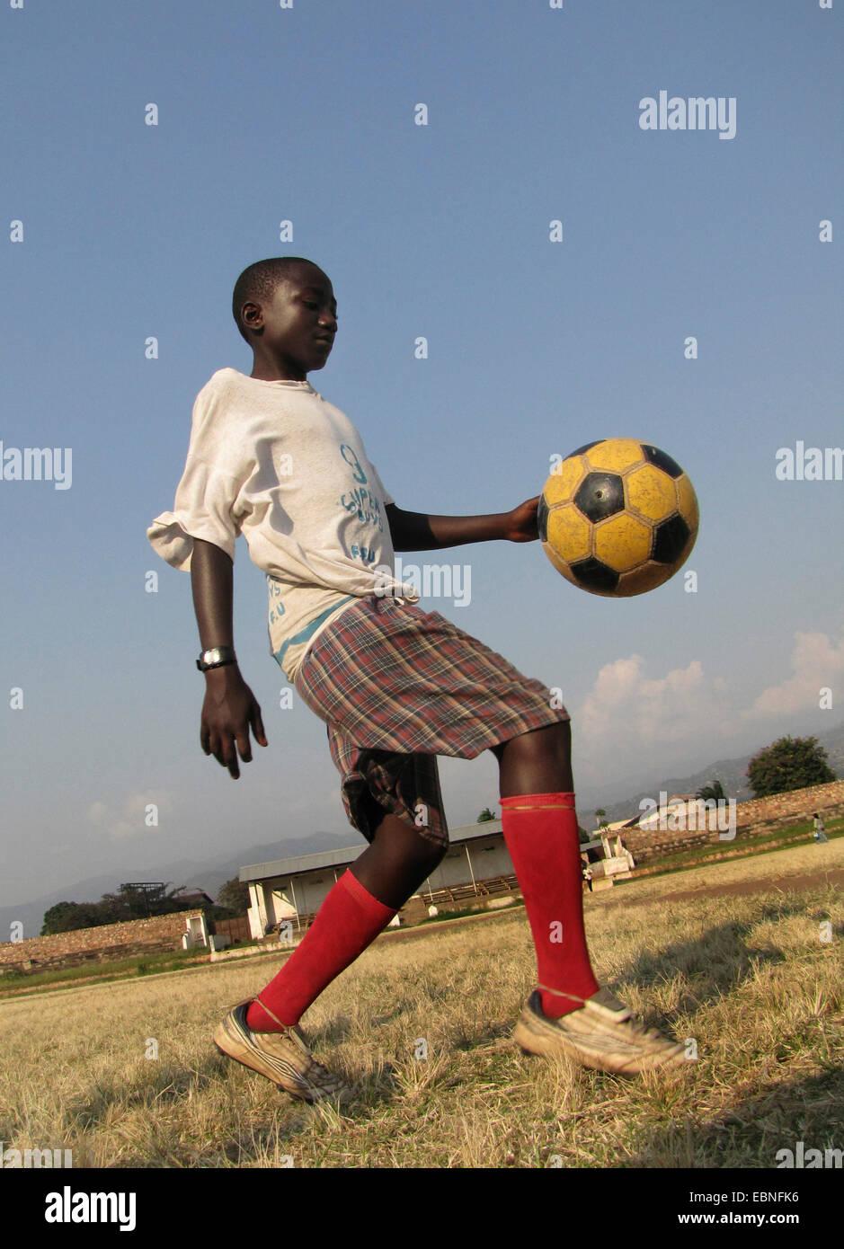 boy playing football in the city's old football stadium, Burundi, Bujumbura mairie, Bujumbura - Stock Image