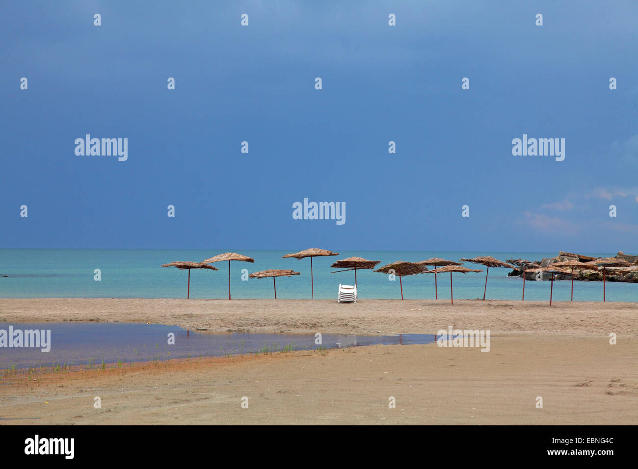 unpopulated beach with sunshades in Bolata bay at approaching rain, Bulgaria, Kaliakra - Stock Image