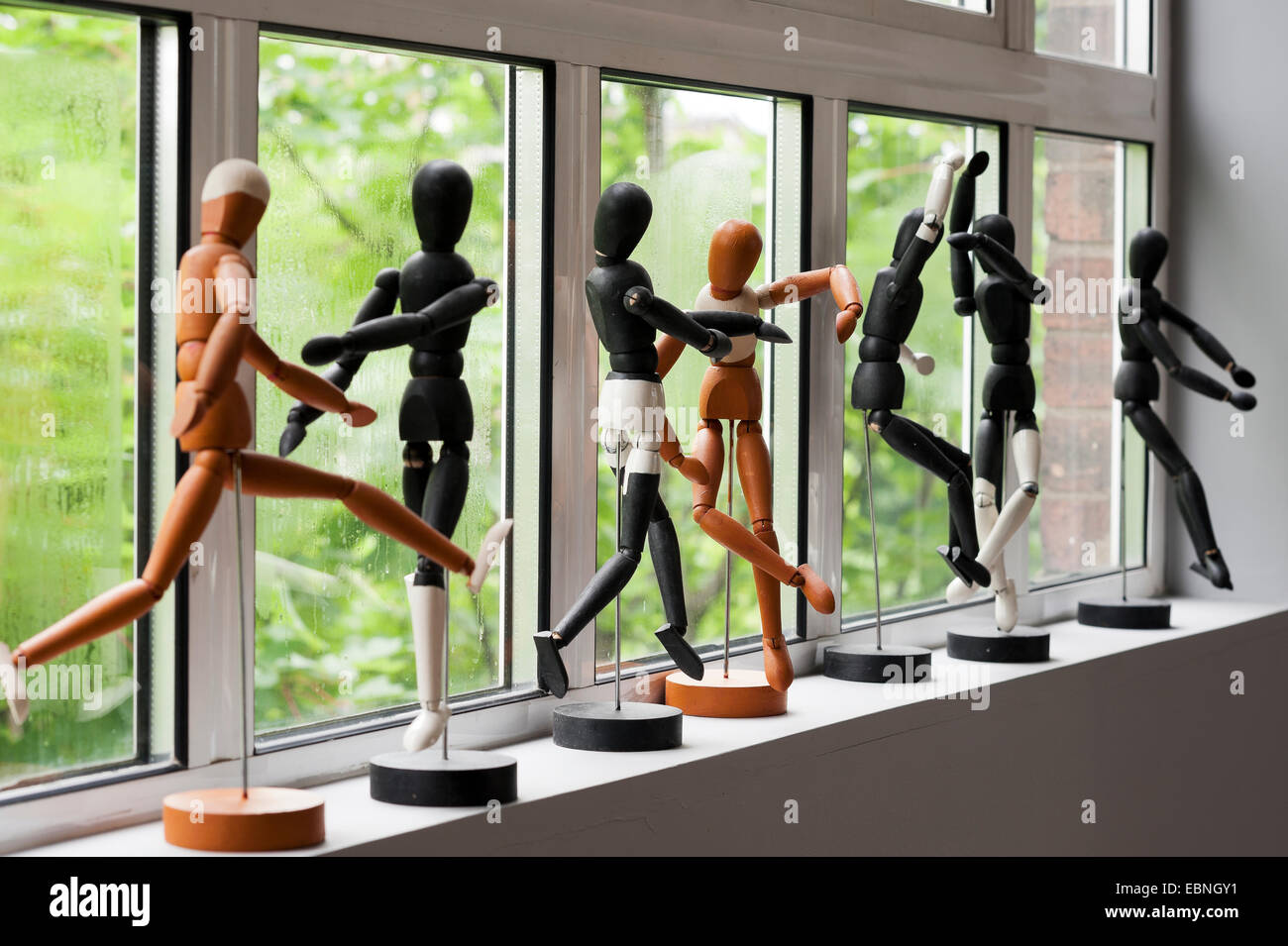 Row of artist mannequins along windowsill. - Stock Image