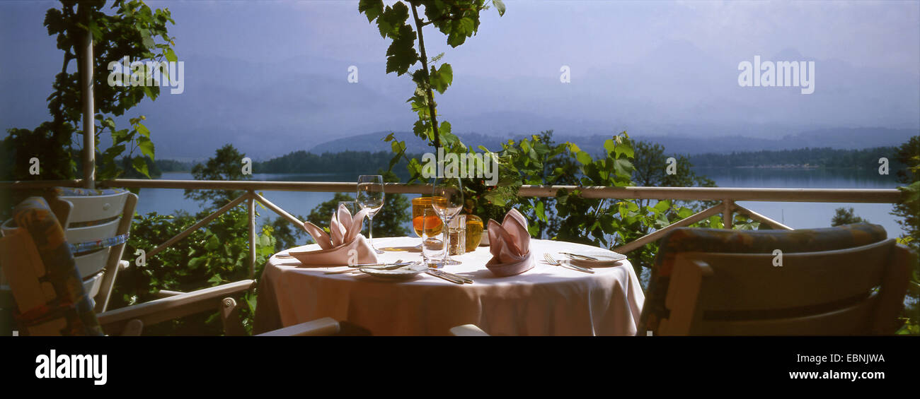 terrace with well-laid table and a view of the lake, Austria - Stock Image