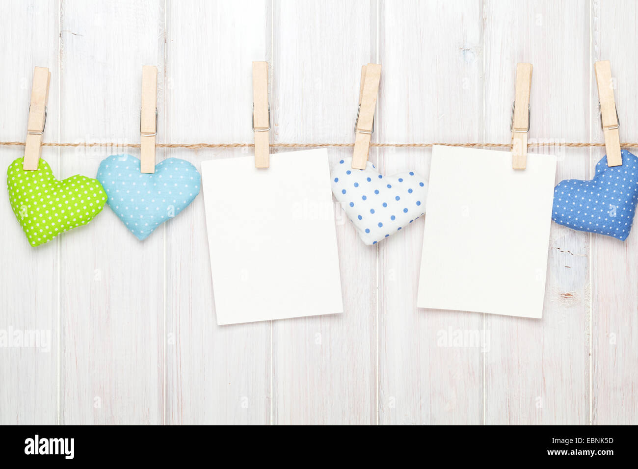 Two photo frames and valentines day toy hearts over white wooden ...
