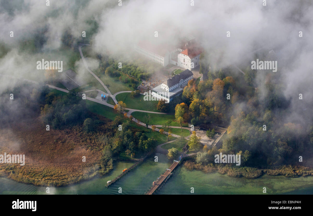 aerial view through the clouds to island Herreninsel with Old Palace and footbridge, Germany, Bavaria, Lake Chiemsee Stock Photo