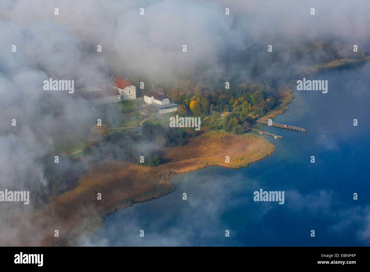 aerial view through the clouds to island Herreninsel with Old Palace and footbridge, Germany, Bavaria, Lake Chiemsee - Stock Image