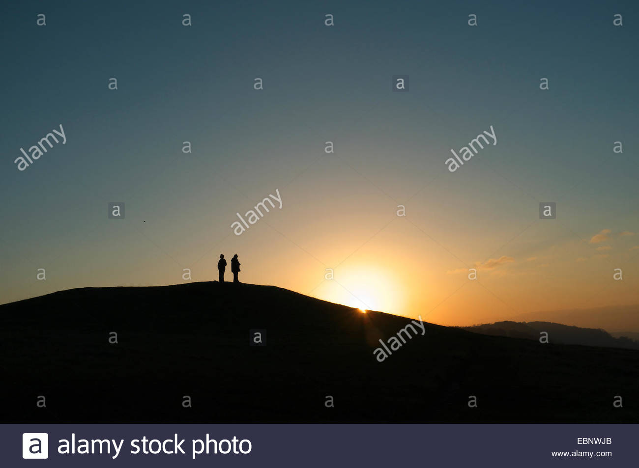 Stroud, Gloucestershire, UK. 3rd December 2014. UK Weather: Two people enjoy watching the sun going down from this Stock Photo