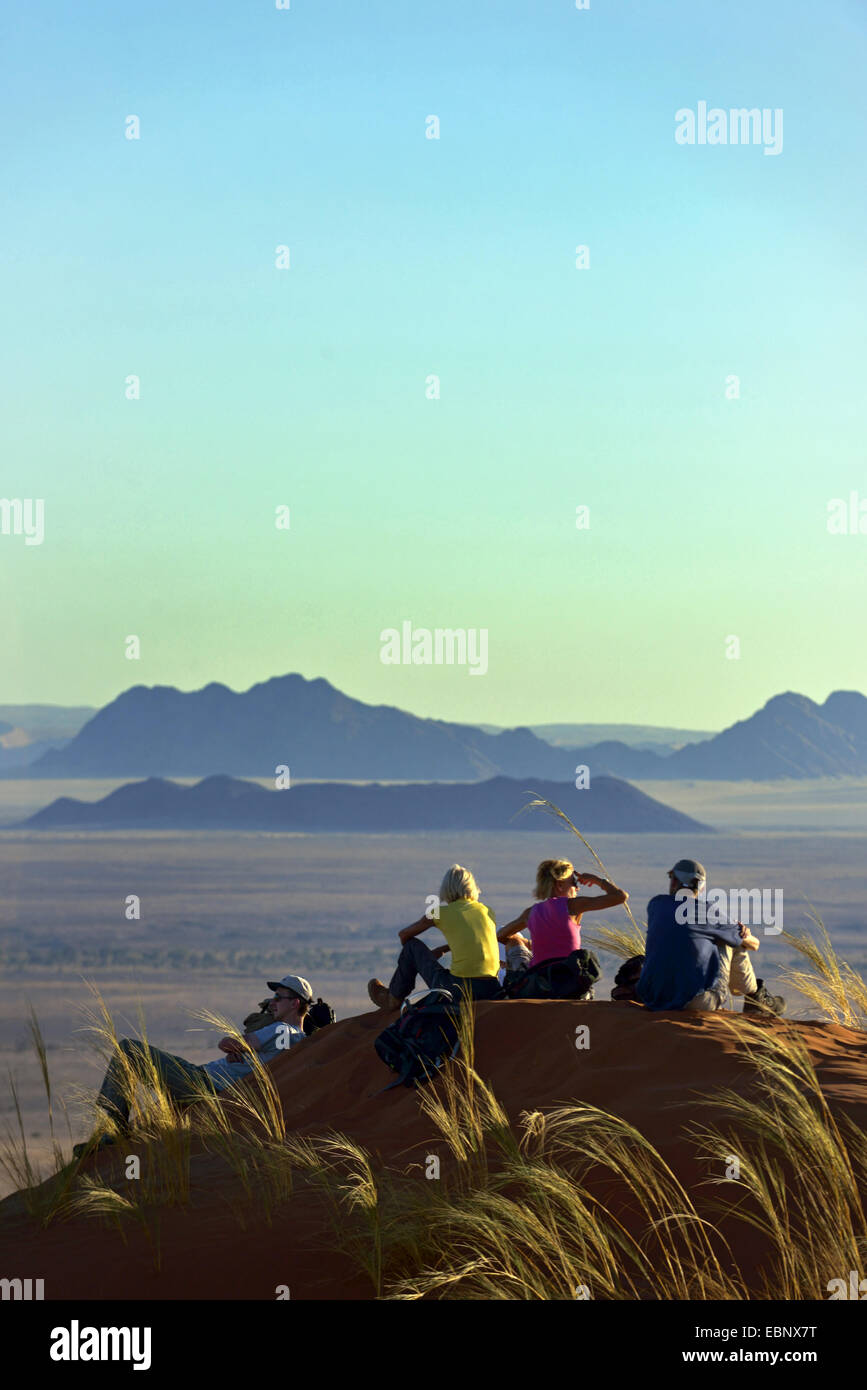 group sitting on a dune in the desert and enjoying the view, Namibia, Namib Naukluft National Park, Sesriem Camp - Stock Image