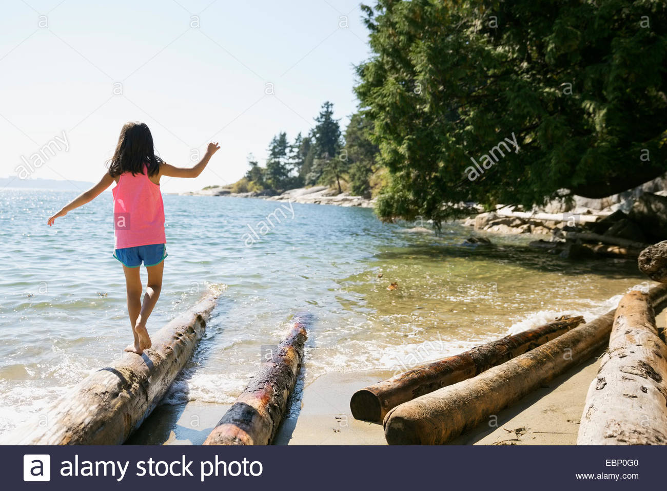 Girl balancing on driftwood at beach - Stock Image