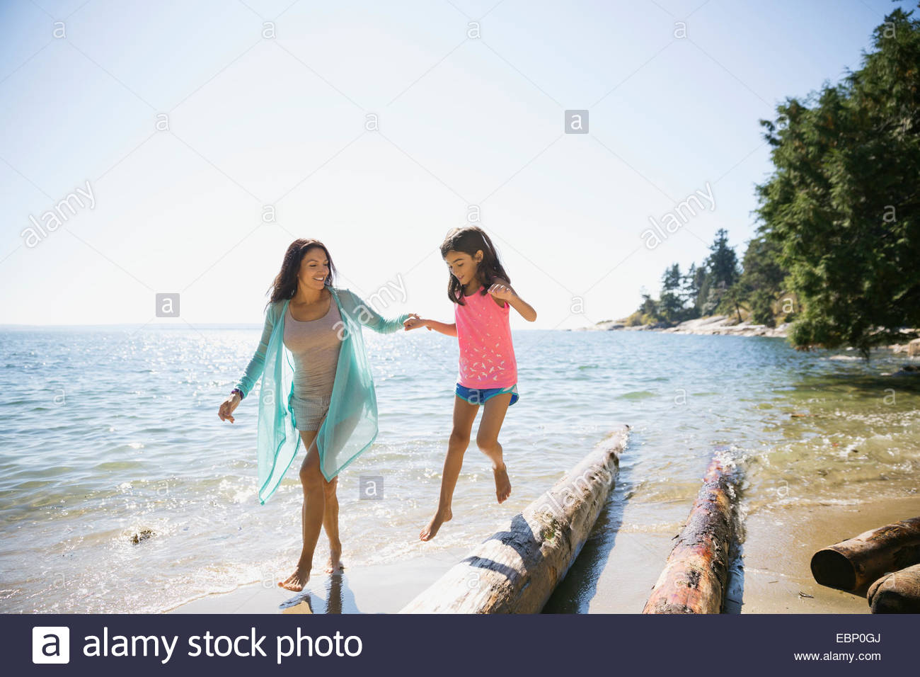 Mother and daughter walking on driftwood at beach - Stock Image