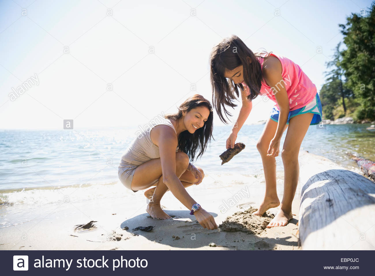 Mother and daughter clam digging on sunny beach - Stock Image
