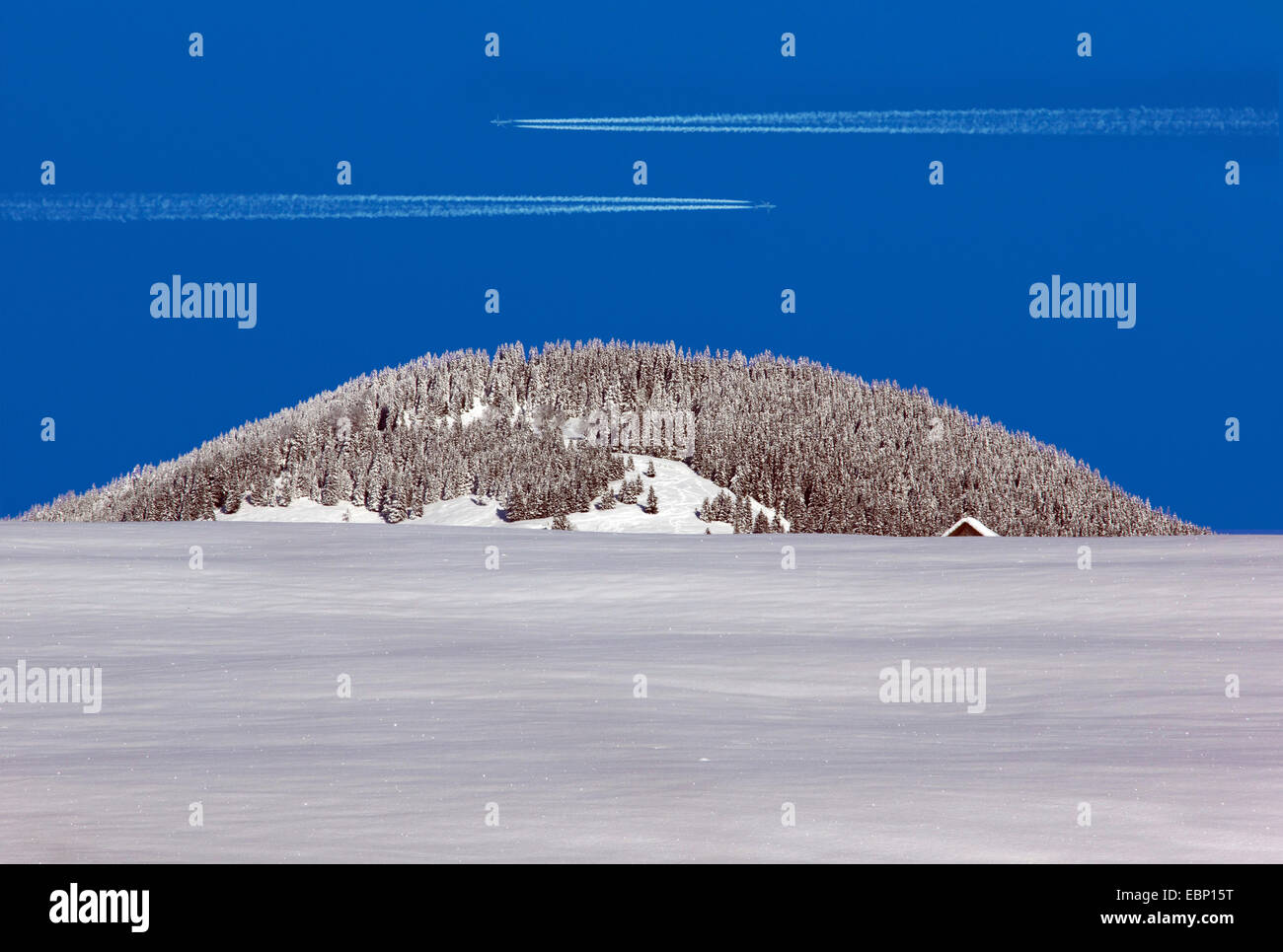 two vapor trails of air planes in blue sky above Hoernle summit in winter, Germany, Bavaria, Oberbayern, Upper Bavaria, - Stock Image
