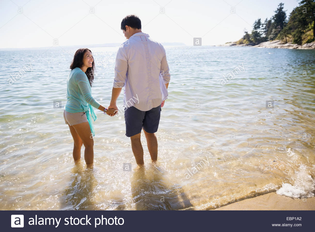 Couple holding hands and wading in ocean Stock Photo