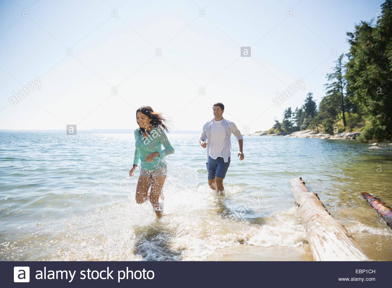 Couple splashing in ocean - Stock Image