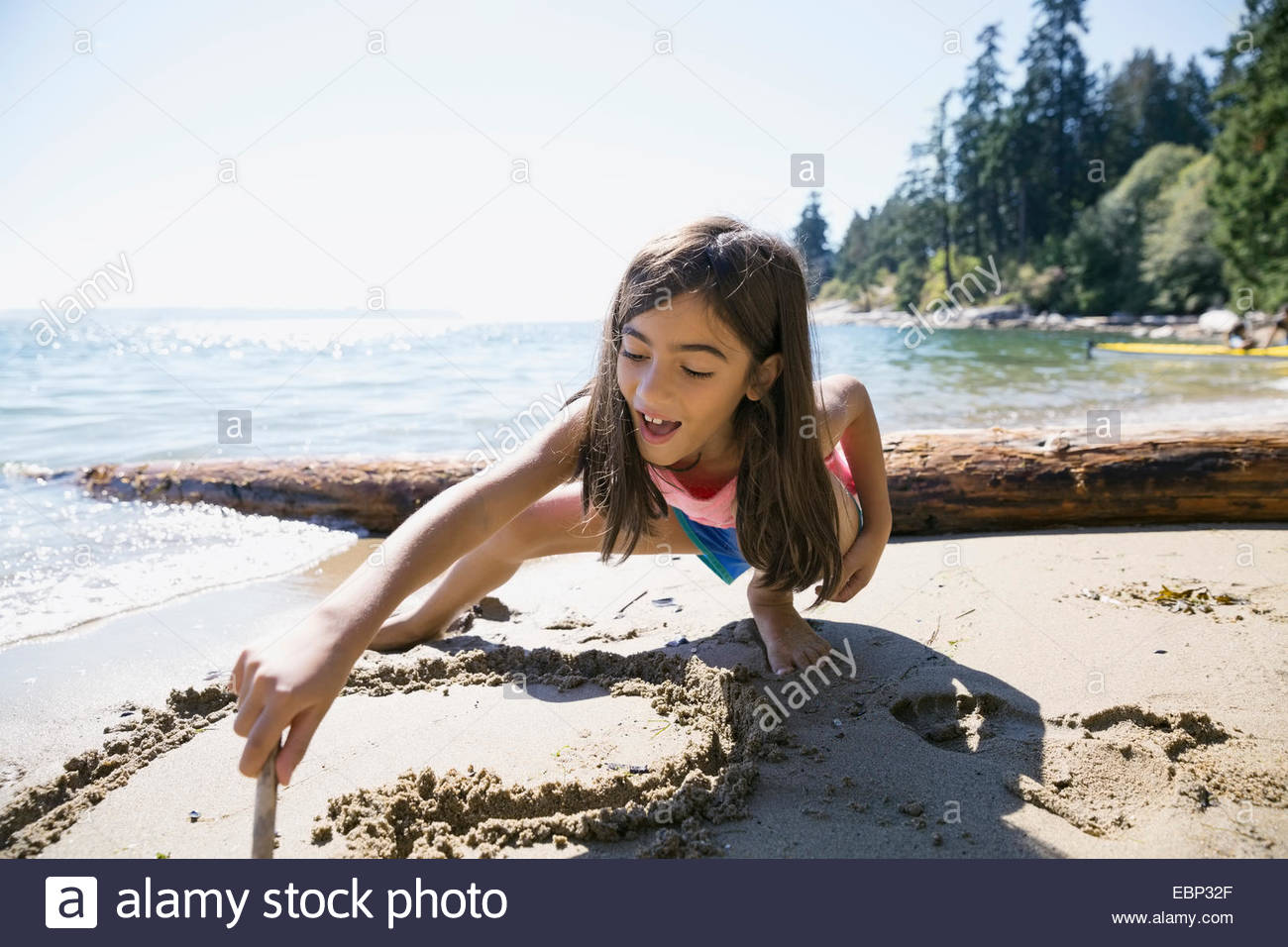 Girl drawing heart-shape in sand on beach - Stock Image