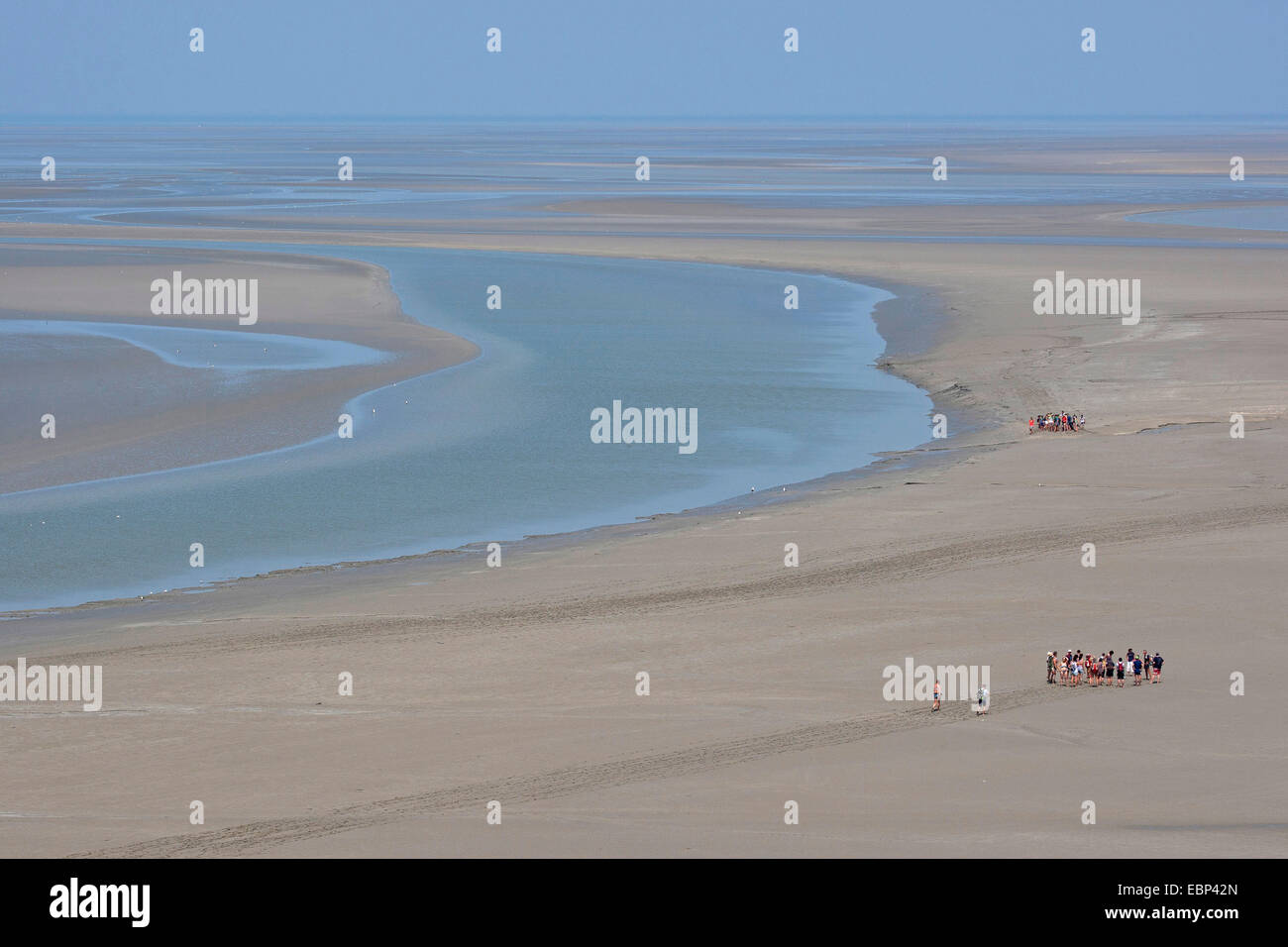 sandy tideland at low tide with tidal flat hikers, France, Brittany - Stock Image