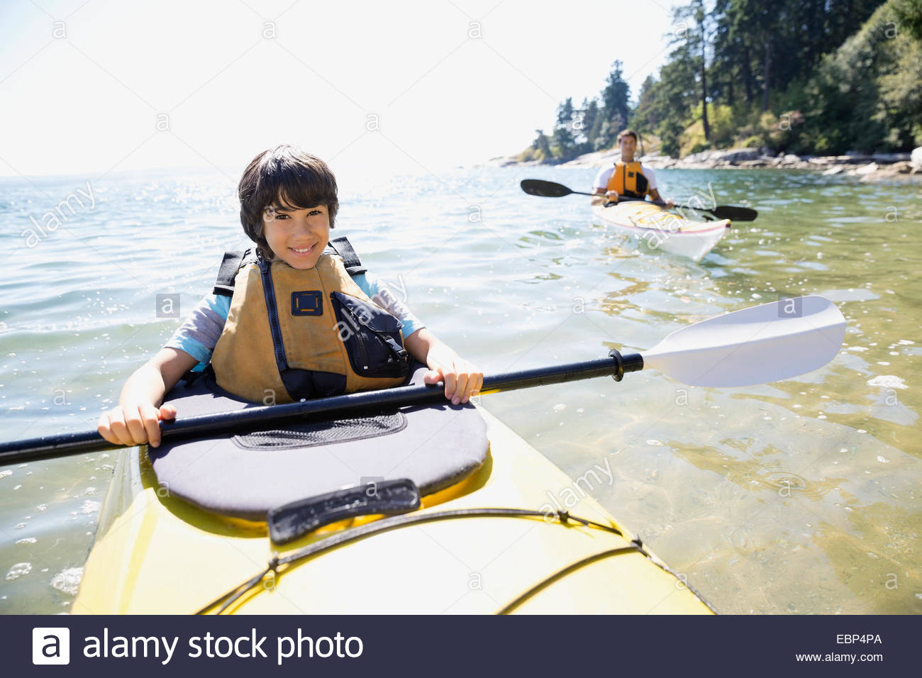 Portrait of father and son kayaking in ocean - Stock Image