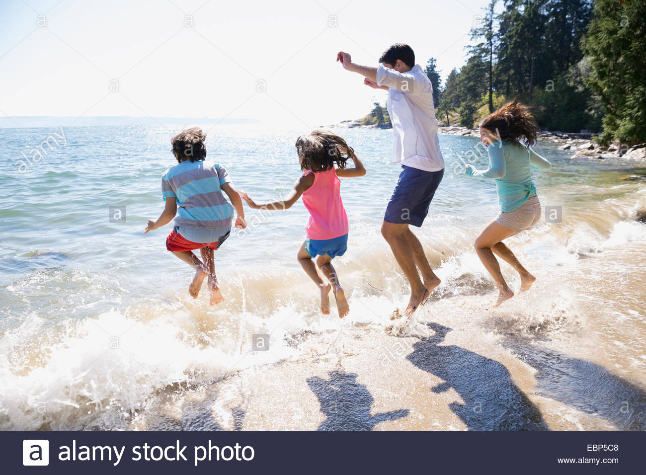 Family splashing in ocean - Stock Image