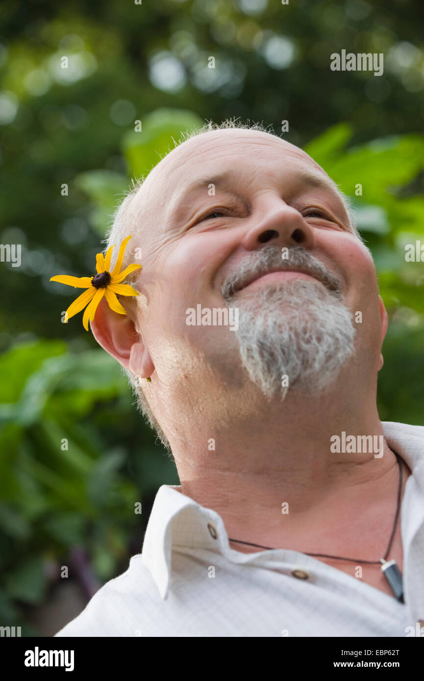 man with flower behind the ear - Stock Image