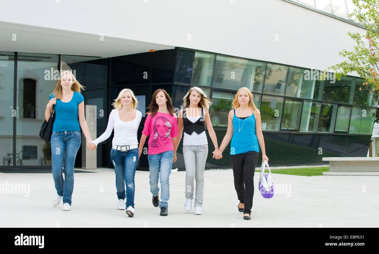 five teenage girls walking over the schoolyard hand in hand - Stock Image