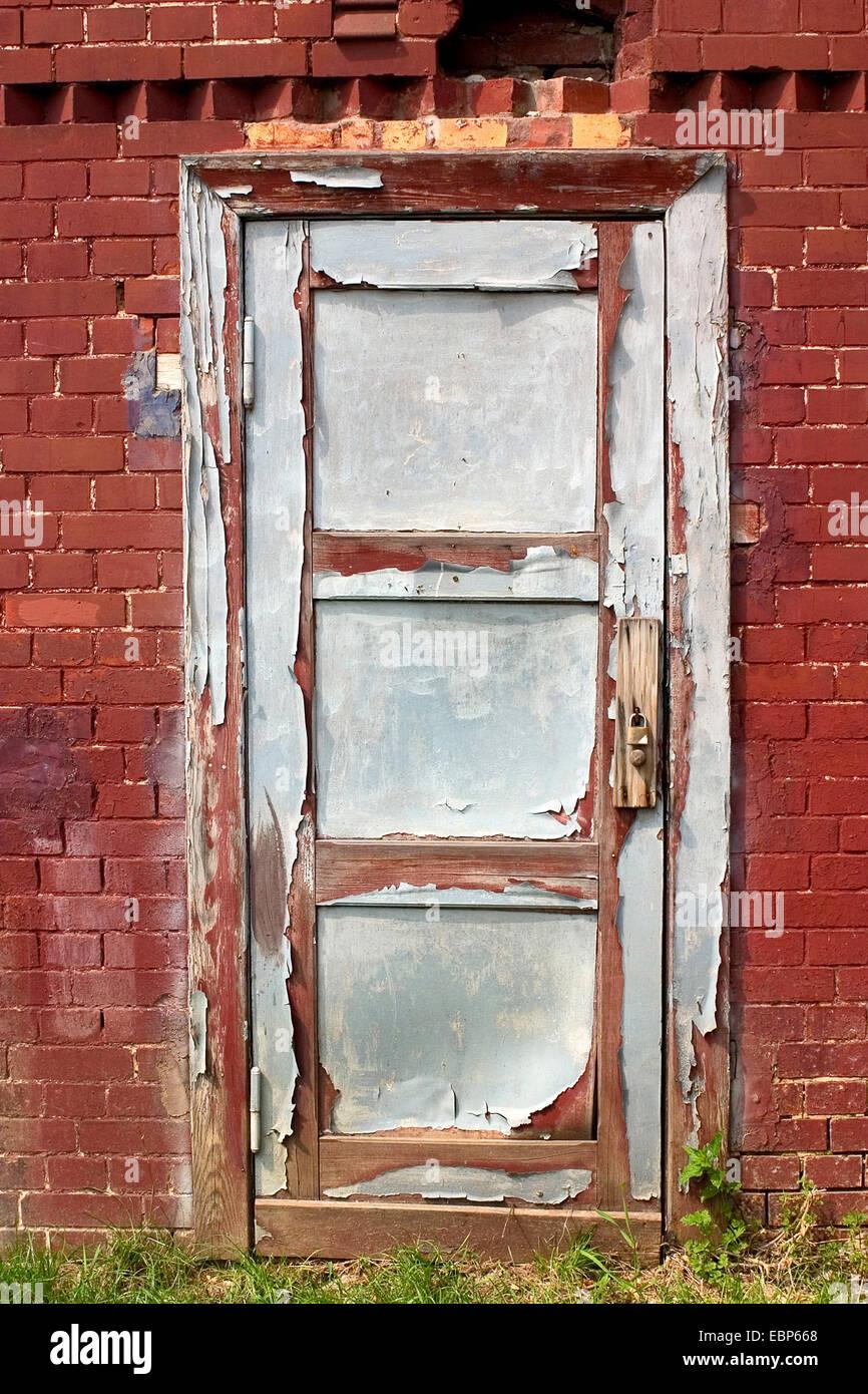 old wooden door of a brick building - Stock Image