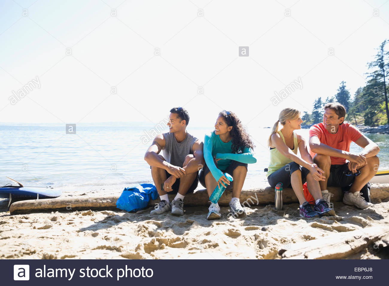 Runners sitting on sunny beach - Stock Image