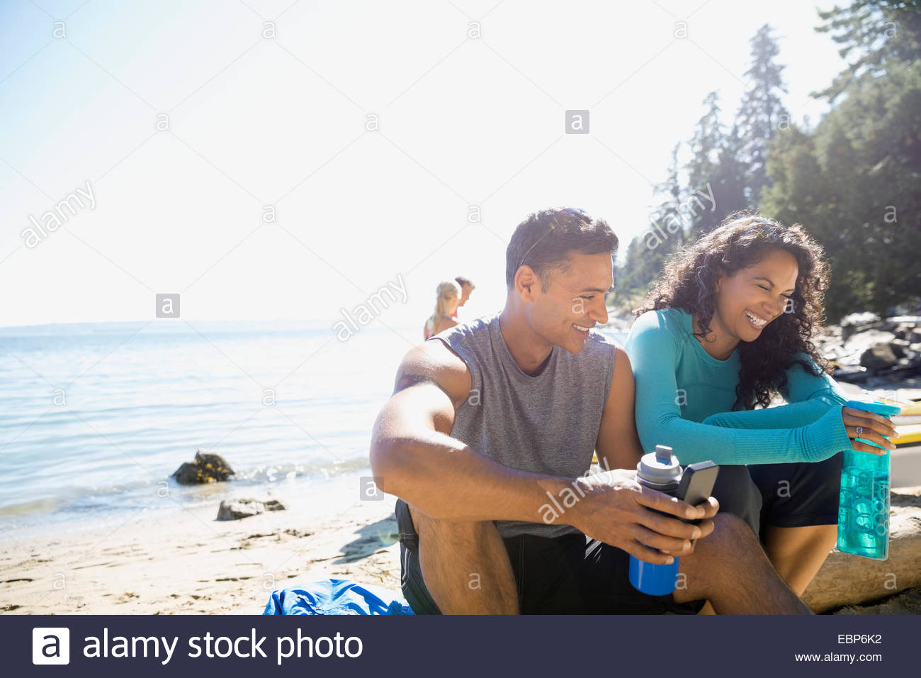 Runners sitting on sunny beach with water bottles - Stock Image