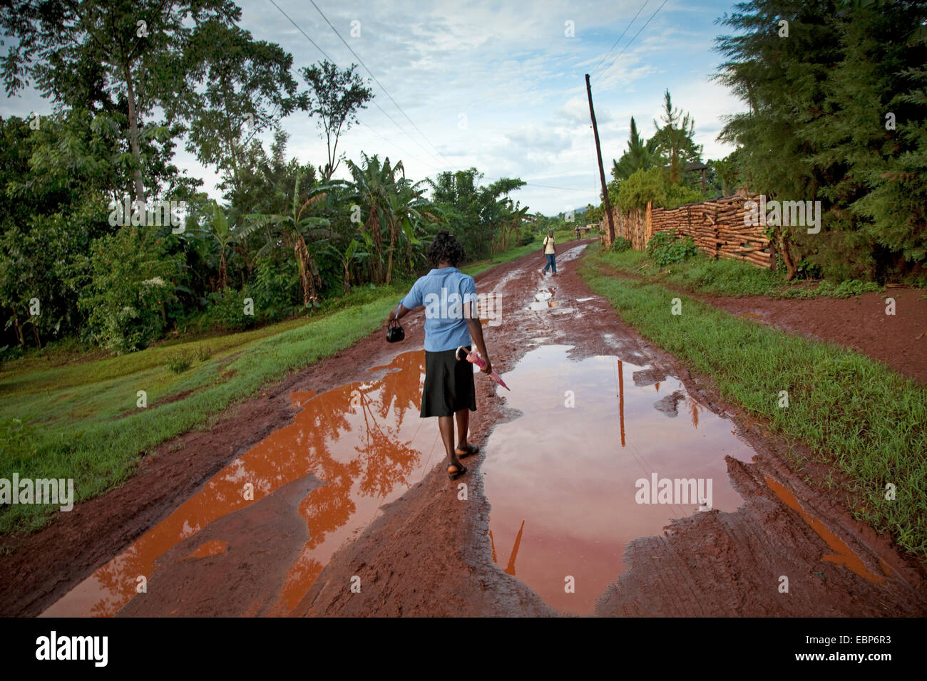 woman with umbrella and handbag is walking on a path that is soaked in water after a recent rainfall, Uganda, Jinja Stock Photo