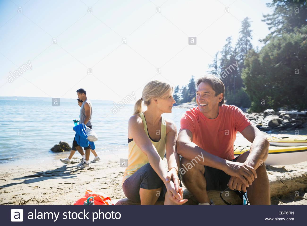Couple talking on sunny beach - Stock Image