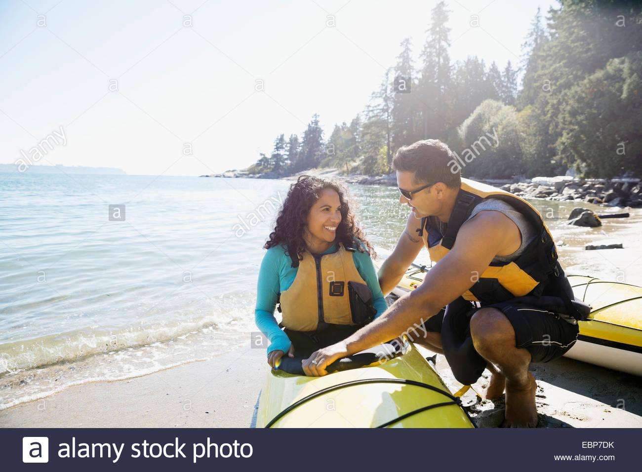 Couple preparing kayaks on sunny beach - Stock Image
