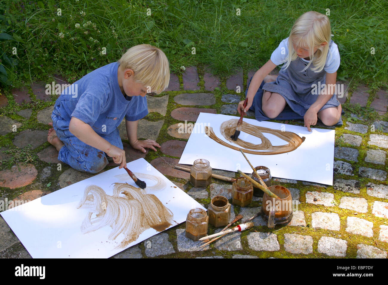 two children painting with earth colour, Germany - Stock Image