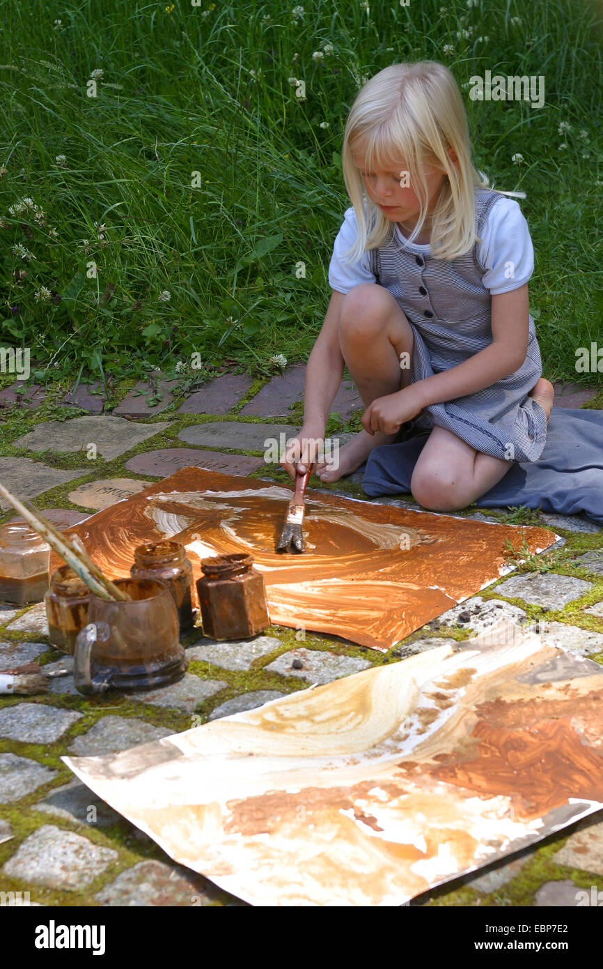 a girl painting with earth colour, Germany - Stock Image