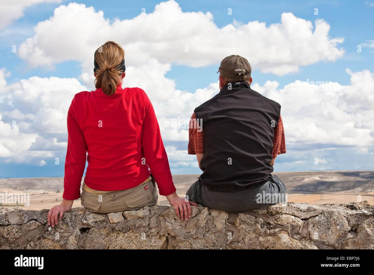 two pilgrims on Camino de Santiago sitting on a wall looking back to Castrojeriz, Spain, Kastilien & Leon, - Stock Image