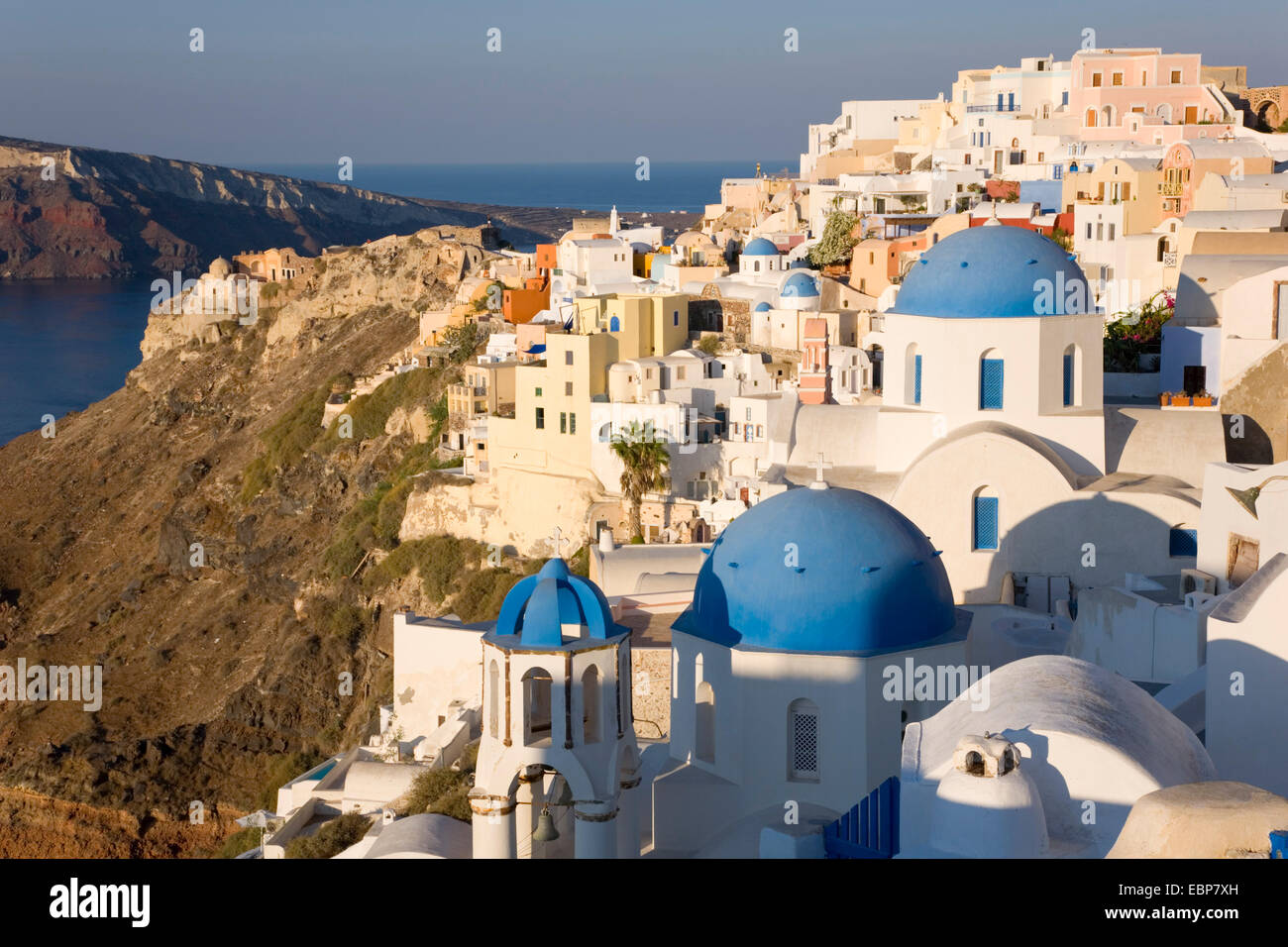 Ia, Santorini, South Aegean, Greece. The village at sunrise, typical blue-domed churches prominent. - Stock Image