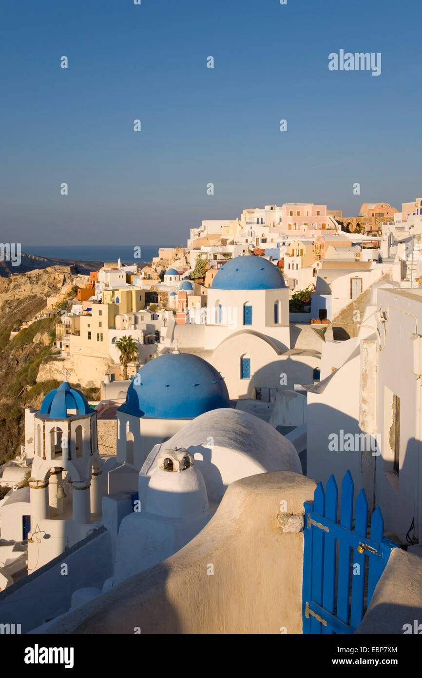 Ia, Santorini, South Aegean, Greece. The village at sunrise, typical blue-domed churches prominent. Stock Photo