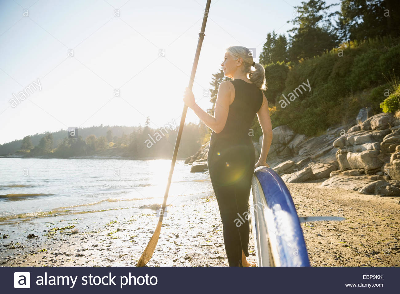 Senior woman with paddle board on sunny beach - Stock Image