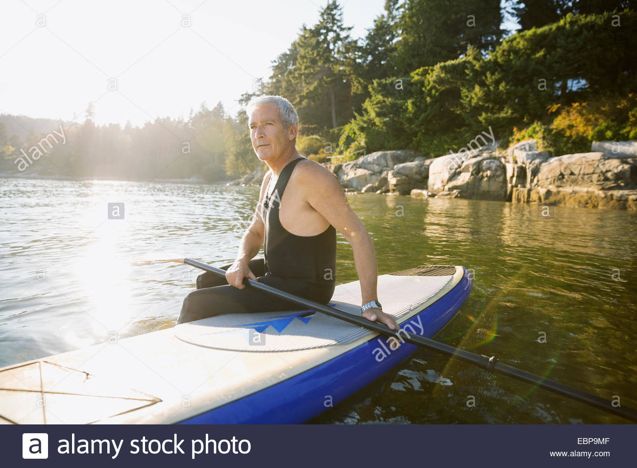 Senior man sitting on paddle board in ocean - Stock Image
