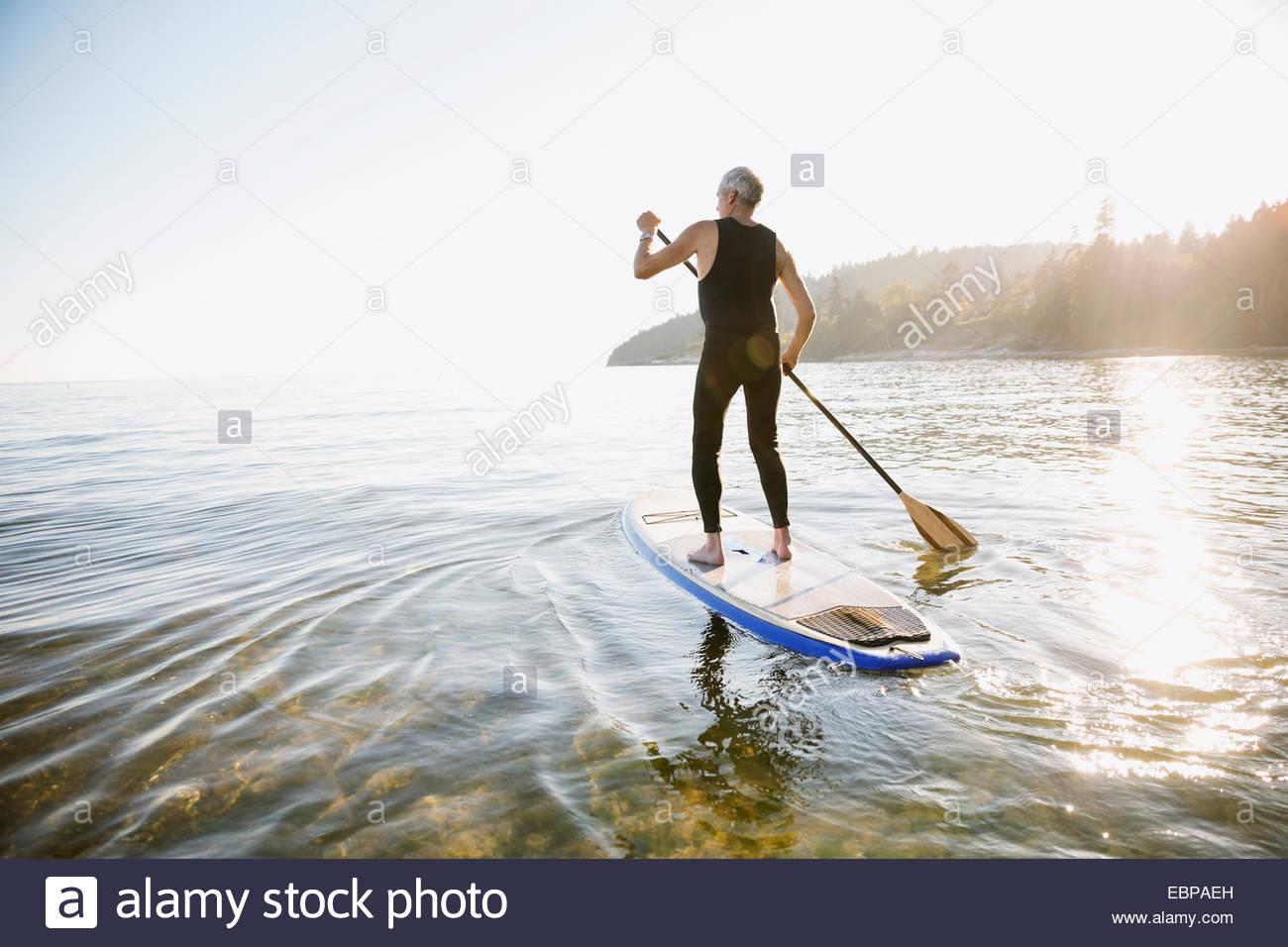 Senior man paddle boarding in ocean - Stock Image