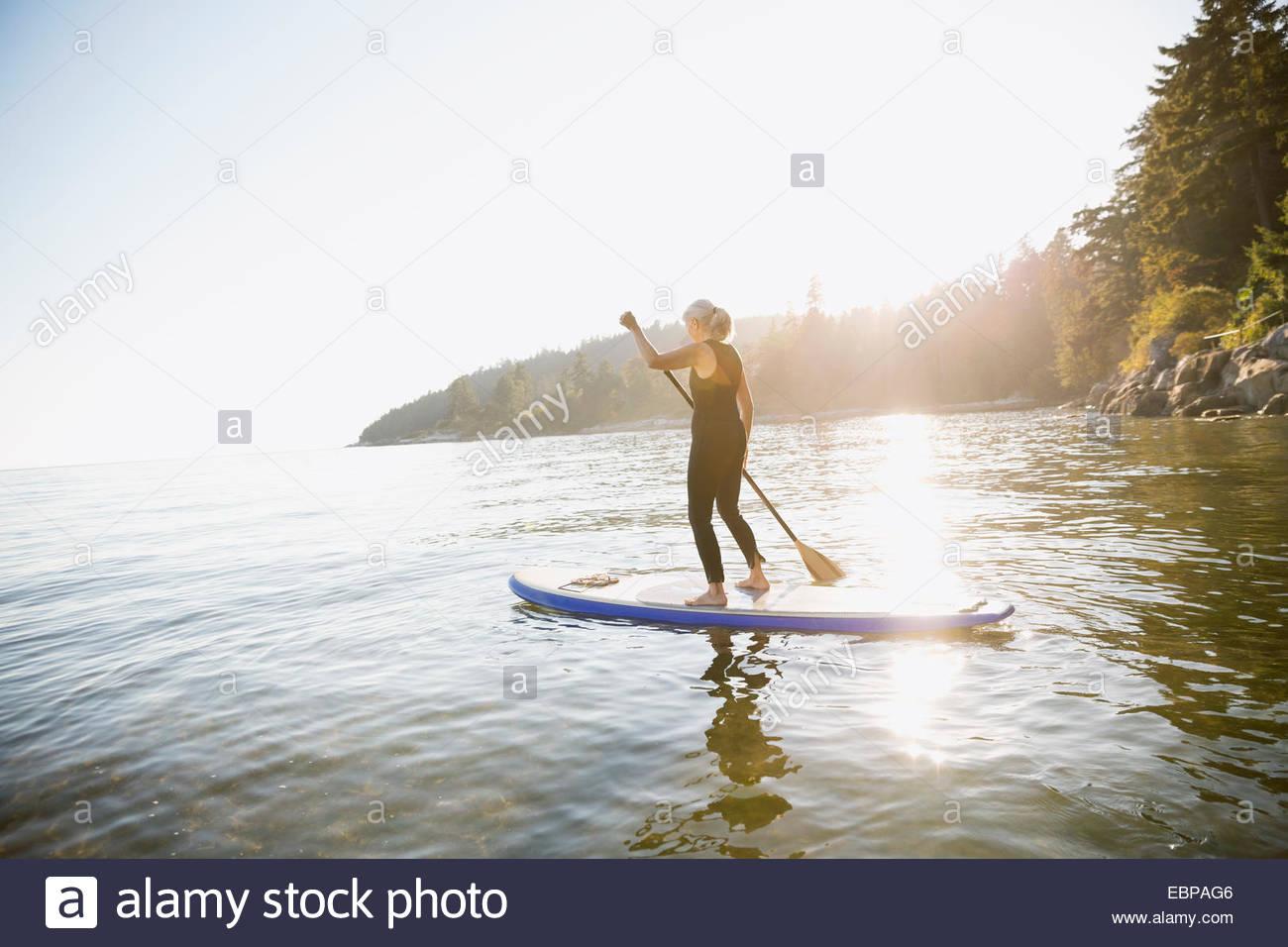 Senior woman paddle boarding in ocean - Stock Image