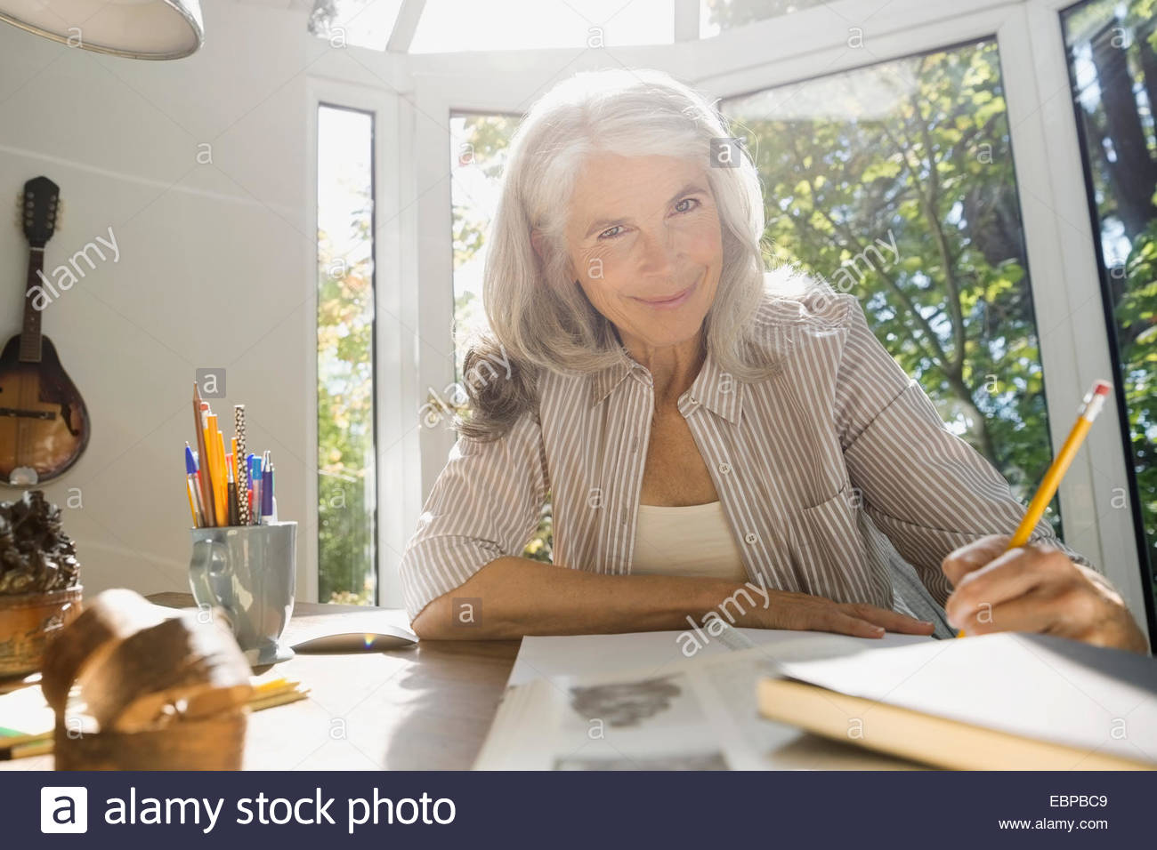 Portrait of senior woman writing in home office - Stock Image