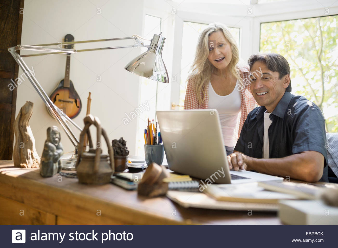 Couple using laptop at desk in home office - Stock Image