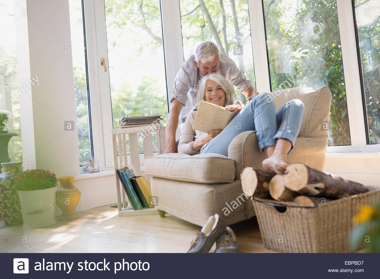 Senior couple reading book in armchair - Stock Image