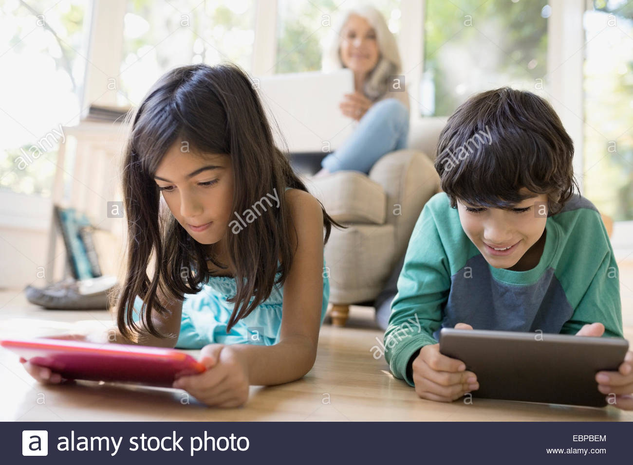Grandmother watching grandchildren use digital tablets - Stock Image