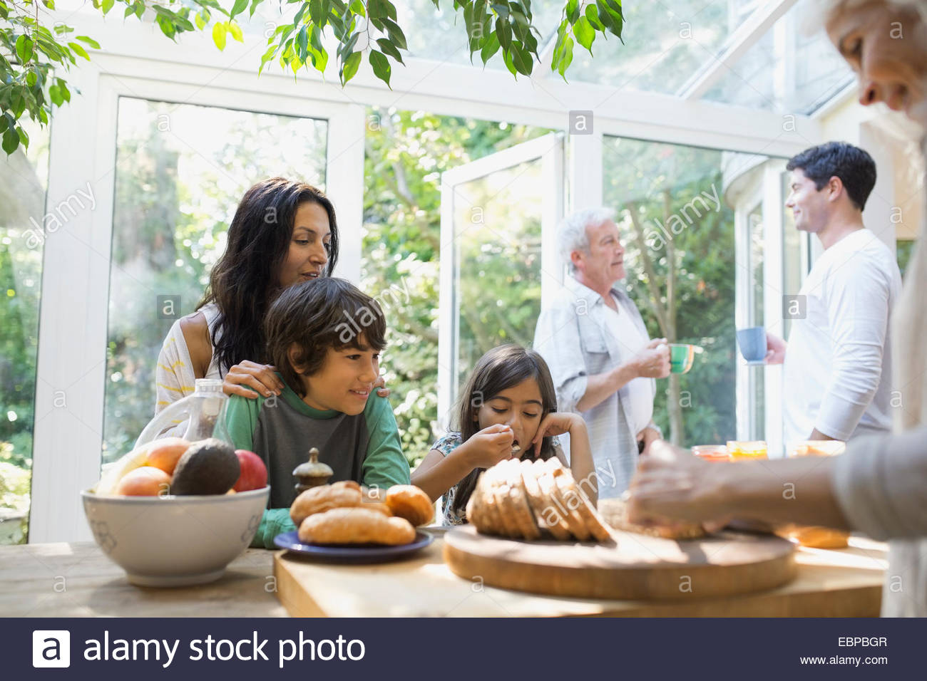 Multi-generation family eating in kitchen - Stock Image