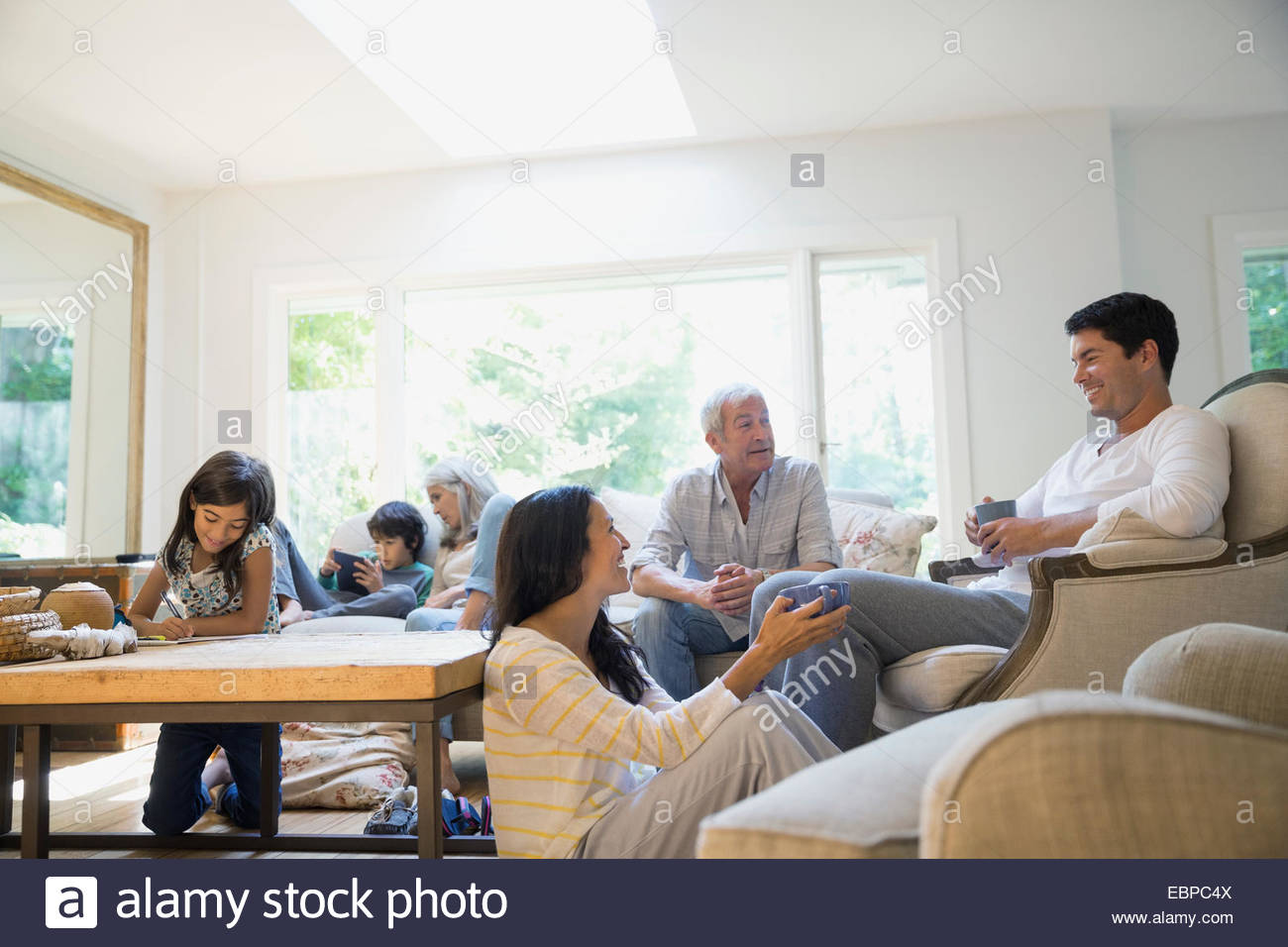 Multi-generation family relaxing in living room - Stock Image