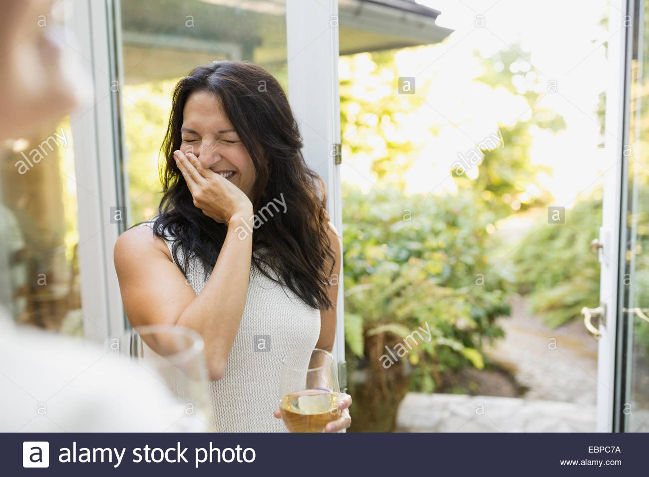 Woman with white wine laughing in kitchen - Stock Image